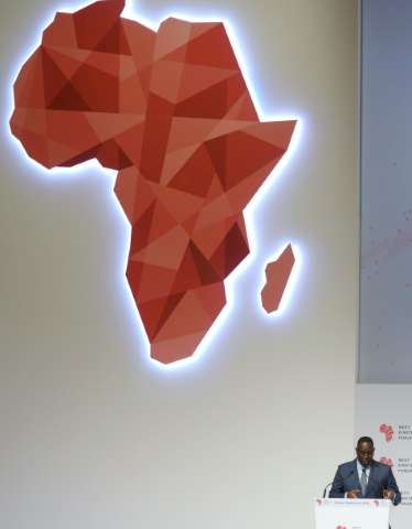 """Senegal President Macky Sall (R) delivers a speech under a map of Africa in Dakar during the opening of the """"Next Einstein"""