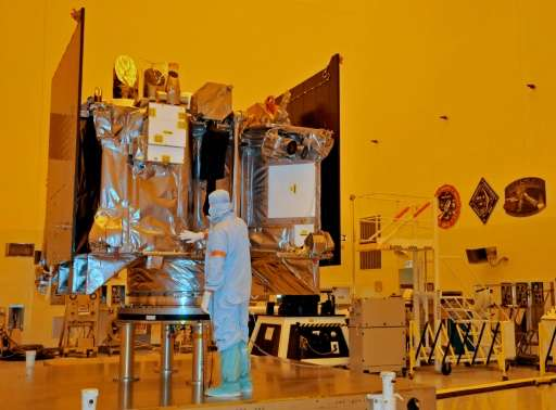 The OSIRIS-REx spacecraft sits on its workstand August 20, 2016 while an engineer checks the protective covering in a servicing