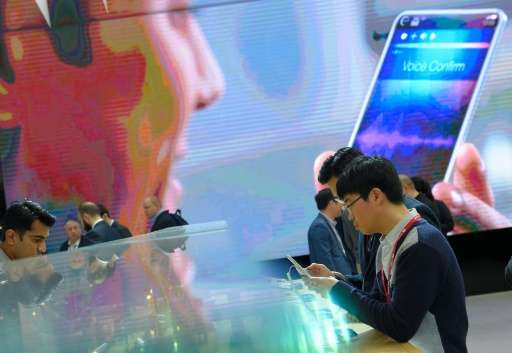 Visitors test smartphones during the Mobile World Congress in Barcelona on February 23, 2016