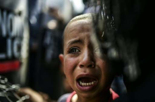 A boy cries during a protest held by migrants and refugees to call for the reopening of the borders at their makeshift camp in t