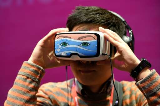 A boy tests the 'Oculus VR' virtual device, at the Deutsche Telekom stand