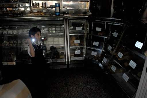 A boy uses a flshlight during a power cut at a bakery in the border state of San Cristobal, 600 km west of Caracas on April 25,