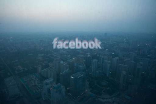 A computer screen displays the logo of social networking site Facebook against the backdrop of the Beijing skyline