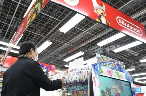 A customer looks at Nintendo video game software at a store in Tokyo