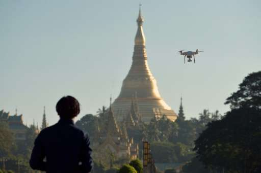 A drone enthusiast is seen piloting his remote controlled craft at a park in Yangon