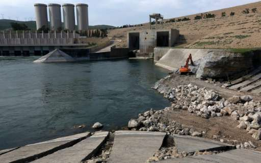 A employee operates an excavator as he works at strengthening the Mosul Dam on the Tigris River
