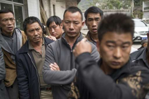 A group of men wait to speak to a journalist in Jinke village, in Pingtang county, after being told to move out of the radio sil