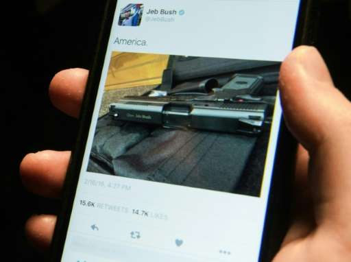 "A man looks at a tweet from US Republican presidential candidate Jeb Bush showing a handgun and the caption ""America"""