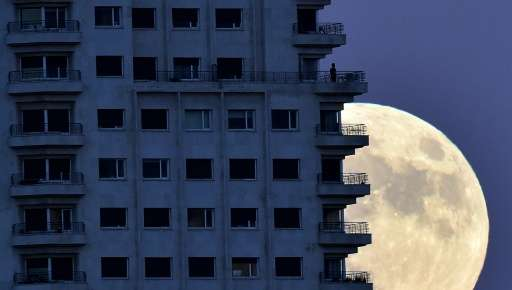 "A man stands on a balcony of a Madrid as the moon rises in background on the eve of a ""supermoon"""