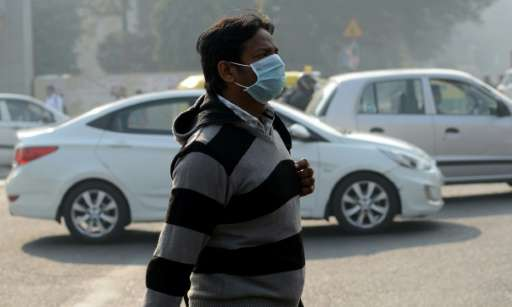 An Indian pedestrian walks with his face covered by a protective mask in New Delhi on December 31, 2015, the day before an exper