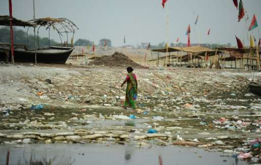 An Indian woman walks amogst plastic bags and garbage strewn on the banks of the River Ganges at Sangam, the confluence of the G