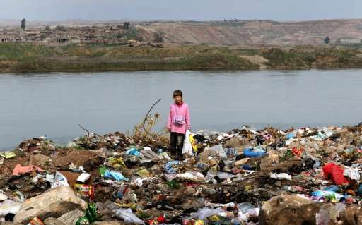 An Iraqi girl stands amid garbage on the banks of the Tigris River in the village of Wana, some 10 kms south of the Mosul Dam