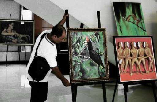 ‌A painter arranges a painting of a rare hornbill species during an exhibition in Pontianak, West Kalimantan province