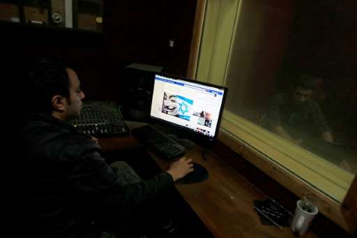 "A Palestinian man looks at Facebook page with a picture depicting the ""#Op_Israel"" campaign launched by the activist g"