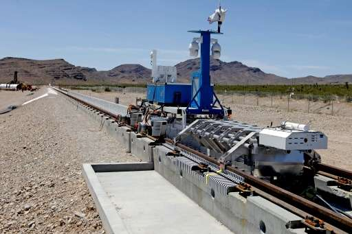 A recovery vehicle and a test sled sit on rails after the first test of the propulsion system at the Hyperloop One Test and Safe