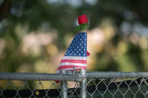 A rose and flag stand atop a fence surrounding the scene of the massacre in San Bernardino, California, December 21, 2015