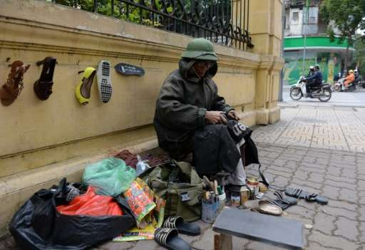 A street cobbler repairs shoes in Hanoi, which experienced its coldest weather for two decades over the weekend according to sta