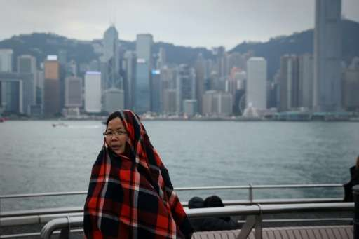 A woman on a viewing deck next to Victoria Harbour in the Tsim Sha Tsui district of Hong Kong keeps warm by wrapping herself a b