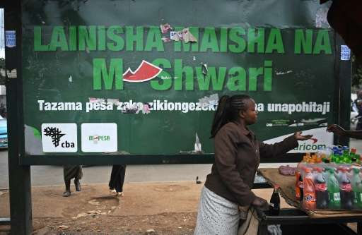 A woman sells beverages at a bus stop near an advertisement for a mobile hone-based banking service, in the Kenyan capital Nairo