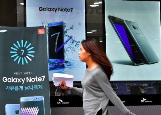 A woman walks past billboards of Samsung Galaxy Note 7 and Galaxy S7 at a mobile phone shop in Seoul on September 12, 2016
