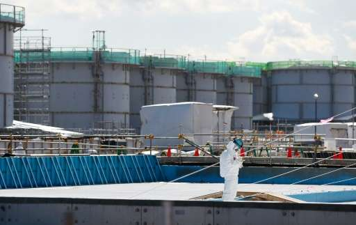 A worker wearing a protective suit and mask takes notes in front of storage tanks for radioactive water, during a media tour at