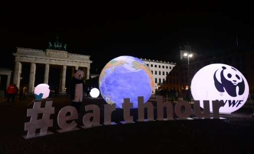 A WWF activist dressed as a panda bear stands next to an illuminated globe in front of the darkened Brandenburger Gate in Berlin