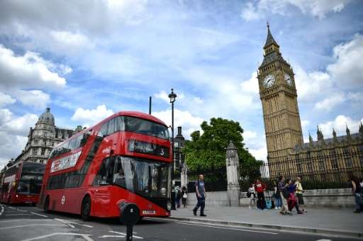 Buses pass the Houses of Parliament in London
