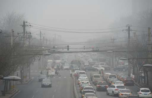 Cars driving below a blanket of smog on a heavily polluted day in Beijing