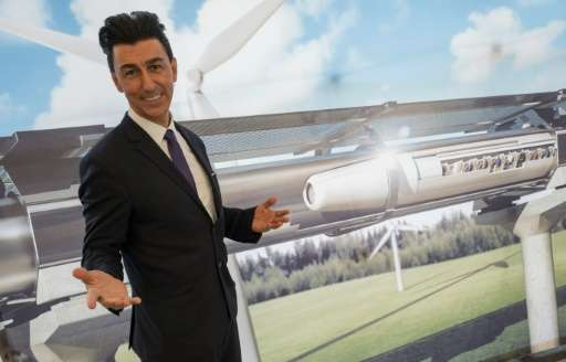 Chairman of Hyperloop Transportation Technologies Inc Bibop Gresta poses in front of a rendering of the Hyperloop technology, at