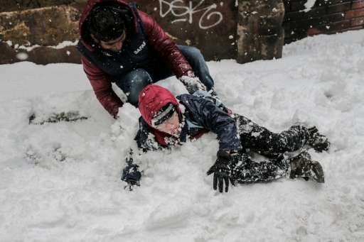 Children play in the snow in Istanbul on December 31, 2015