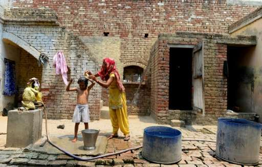 Divya Rathi washes her daughter with contaminated water near their house in the village of Gangnauli, in India's northern state