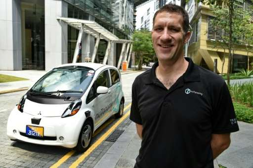 Doug Parker, COO of nuTonomy, the developer of the software for driverless taxis, pictured alongside one of the vehicles during