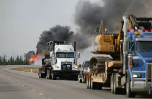 Flames rise off Highway 63 on May 7, 2016 outside Fort McMurray, where raging forest fires have forced more than 88,000 from the