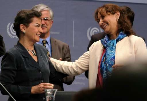 French Environment minister Segolene Royal (right) hands over a gift to Christiana Figueres—Executive Secretary of the United Na