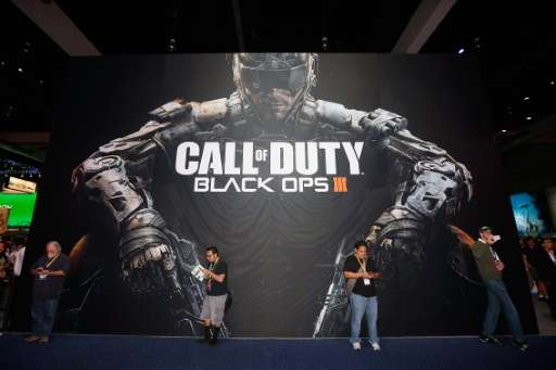 Game enthusiasts stand against a 'Call of Duty Black Ops 3' advertisment during the Annual Gaming Industry Conference E3 at the