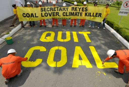Greenpeace activists demonstrate on the driveway of the Department of Energy in Manila