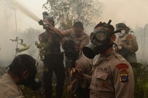 Indonesian police and firefighters extinguish a fire on burning peat land in Central Kalimantan province on Borneo island