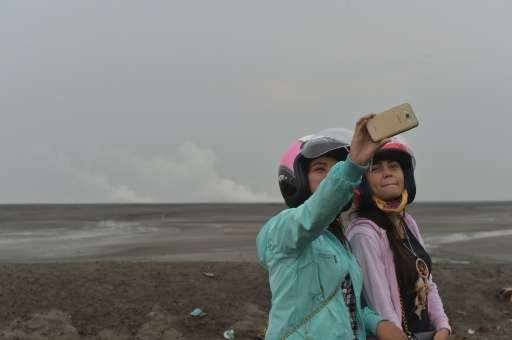 Indonesian tourists take selfies in Sidoarjo, East Java, where a mud volcano erupted in May 2006 swallowing entire villages
