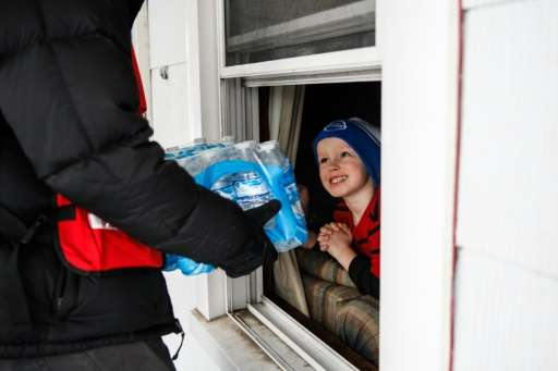 Jake McSigue receives a package of bottled water through the window of his grandma's home on January 21, 2016 in Flint, Michigan