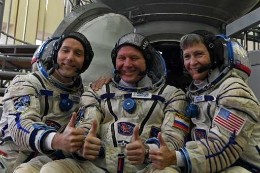 (L-R): France's astronaut Thomas Pesquet, Russia's cosmonaut Oleg Novitsky and US astronaut Peggy Whitson in front of a Soyuz sp