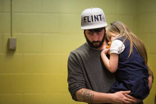 Matt Hopper comforts Nyla Hopper, age 5 of Flint, after she has her blood drawn to be tested for lead at Eisenhower Elementary S