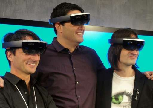 Microsoft executives Joe Belfiore (L), Terry Myerson (C) and Alex Kipman (R) wear HoloLens eyewear that overlays 3D images on th