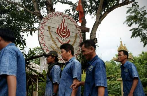 Pa Deng village elders walk past a clean energy sign given to them by Thailand's Ministry of Energy