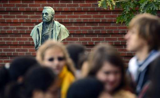 People crowd in front of a statue of Swedish inventor Alfred Nobel at the Karolinska Institute in Stockholm