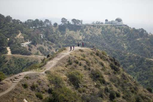 People hike along a ridge overlooking the Griffith Observatory where vegetation is drying out due to lack of rain, in Los Angele