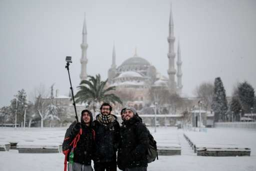 People pose for a selfie during a snowfall in Istanbul on December 31, 2015