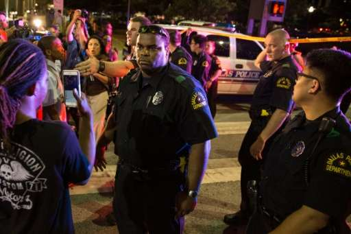 Police attempt to calm the crowd as someone is arrested following the sniper shooting in Dallas on July 7, 2016