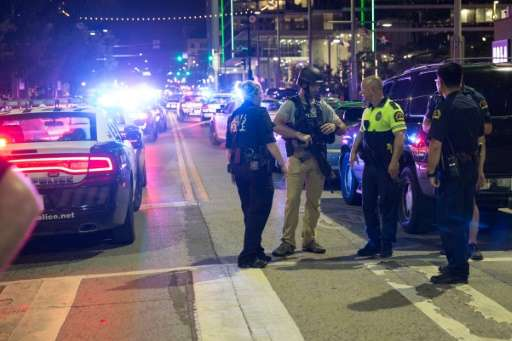 Police stand near a baracade following the sniper shooting in Dallas on Thursday, July 7, 2016