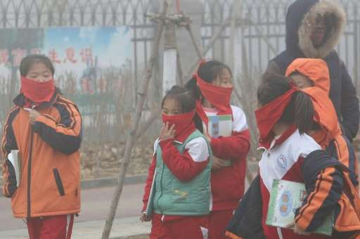 Pupils from an elementary school cover their mouths and noses as they leave the schoolyard after the classes were suspended beca