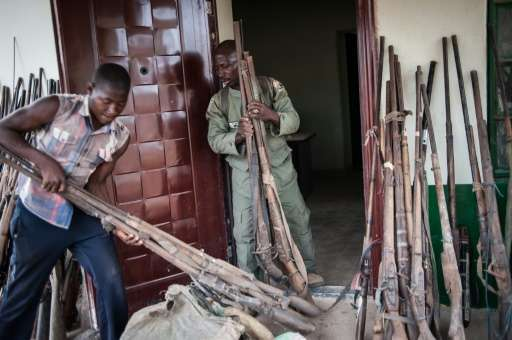 Ranger Hashumu Abdullahi (C), known as 'The Armorer' and his assistant, unpacking some of the over 200 confiscated locally made
